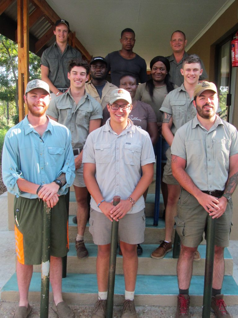 The new NQF Level 2 Dangerous Game Site Guiding course students and an interesting mix. Here they are outside our new classroom with senior trainer Pieter Nel. In their hands they carry their 'rifle' – it'll help them to easily master the handling and shooting of a large calibre rifle, needed for their and their clients' protection in the bush.